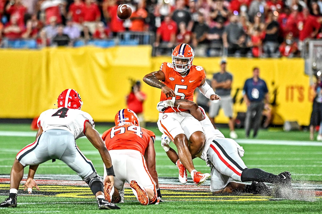zSep 4, 2021; Charlotte, North Carolina, USA; Clemson Tigers quarterback D.J. Uiagalelei (5) is hit while he throws the ball during the second quarter against the Georgia Bulldogs at Bank of America Stadium. Mandatory Credit: Griffin Zetterberg-USA TODAY Sports