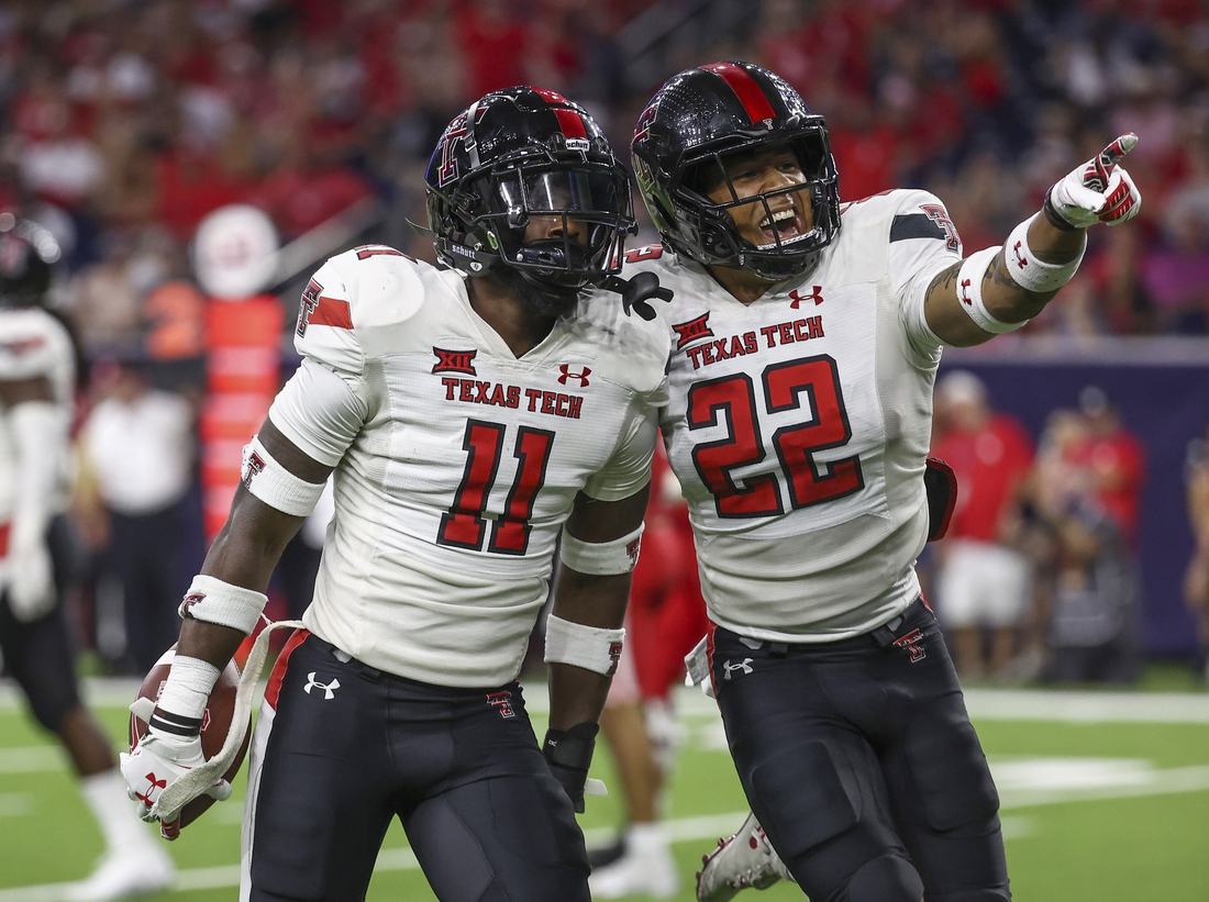 Sep 4, 2021; Houston, Texas, USA; Texas Tech Red Raiders defensive back Eric Monroe (11) celebrates with linebacker Brandon Bouyer-Randle (2) after making an interception against the Houston Cougars during the third quarter at NRG Stadium. Mandatory Credit: Troy Taormina-USA TODAY Sports