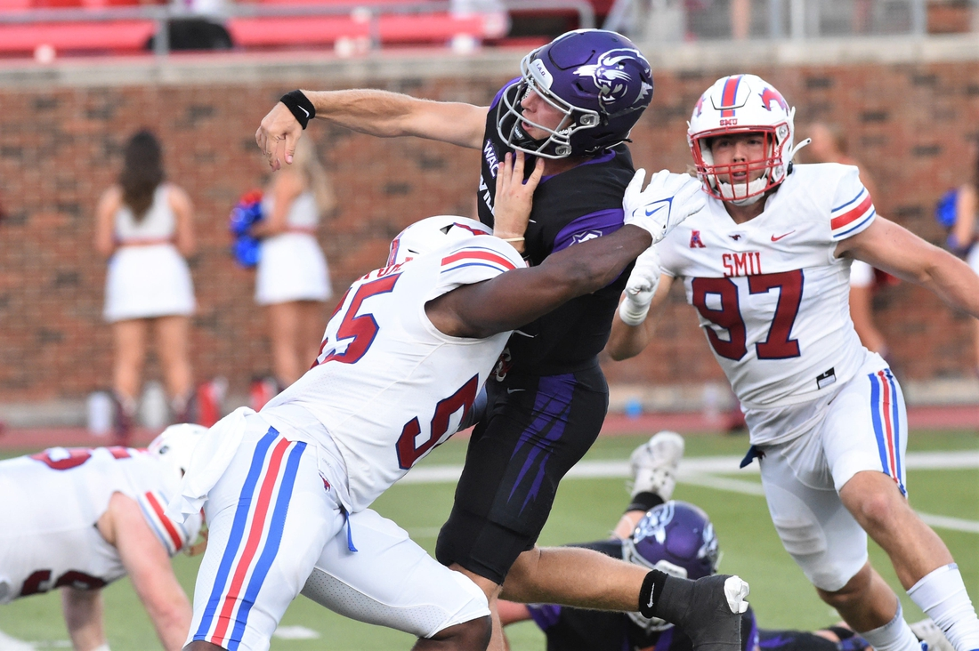ACU quarterback Stone Earle (3) gets hit by SMU's Gary Wiley (55) just after throwing a pass during Saturday's game at Gerald J. Ford Stadium in Dallas on Sept. 4, 2021. The Mustangs won 56-9.  Hof 7539 2