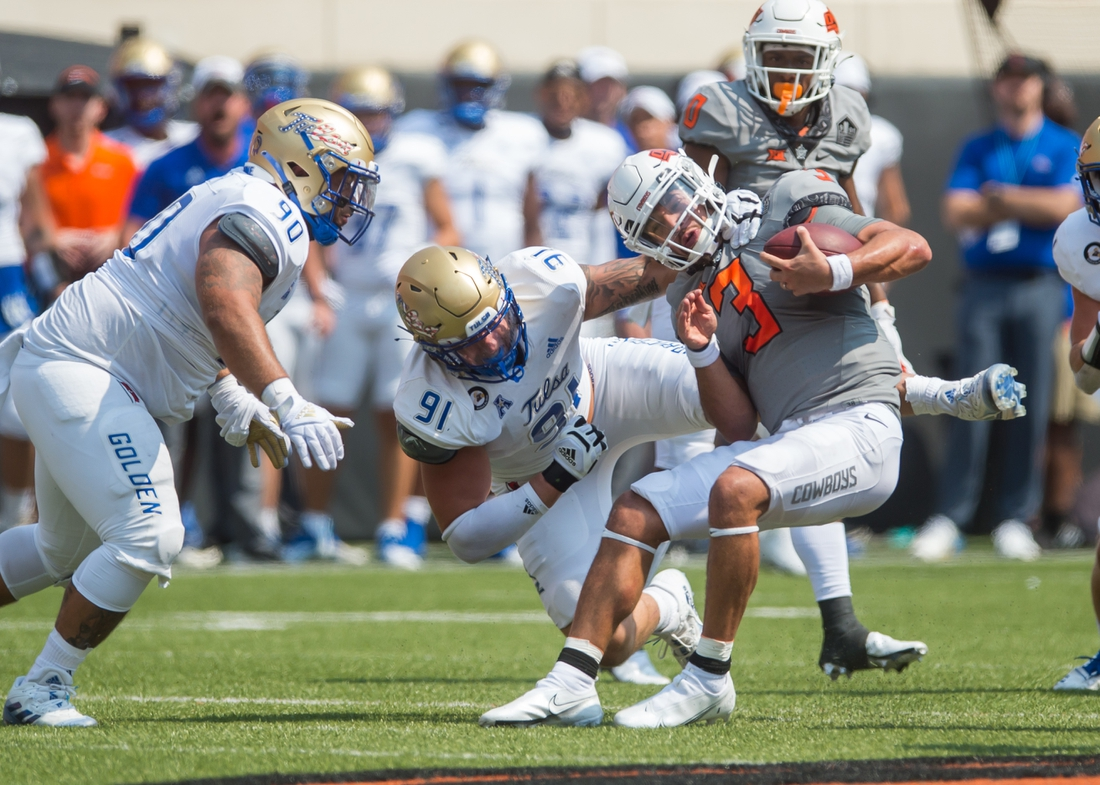 Sep 11, 2021; Stillwater, Oklahoma, USA;  Oklahoma State Cowboys quarterback Spencer Sanders (3) is sacked by Tulsa Golden Hurricane defensive lineman Cullen Wick (91) as defensive lineman Jaxon Player (90) moves in during the second quarter  at Boone Pickens Stadium. Mandatory Credit: Brett Rojo-USA TODAY Sports