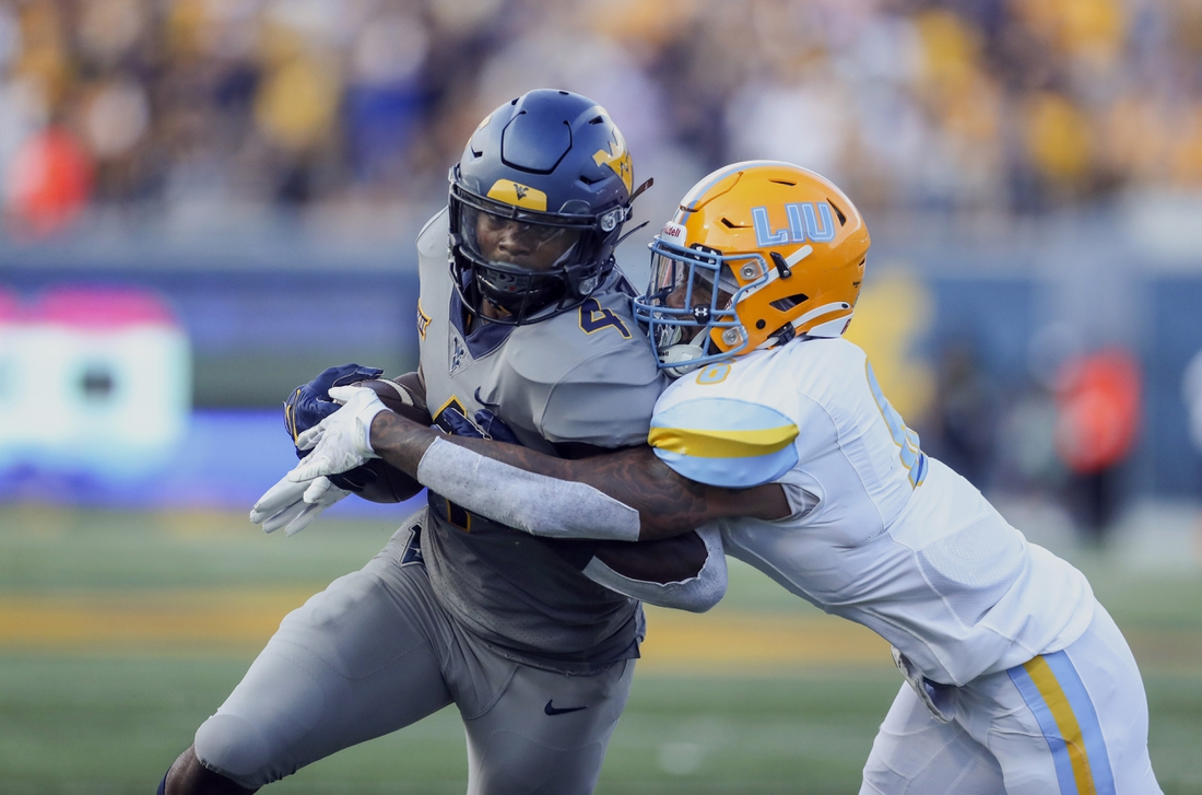 Sep 11, 2021; Morgantown, West Virginia, USA; West Virginia Mountaineers running back Leddie Brown (4) is tackled by Long Island Sharks safety Jerome Brooks III (6) during the second quarter at Mountaineer Field at Milan Puskar Stadium. Mandatory Credit: Ben Queen-USA TODAY Sports