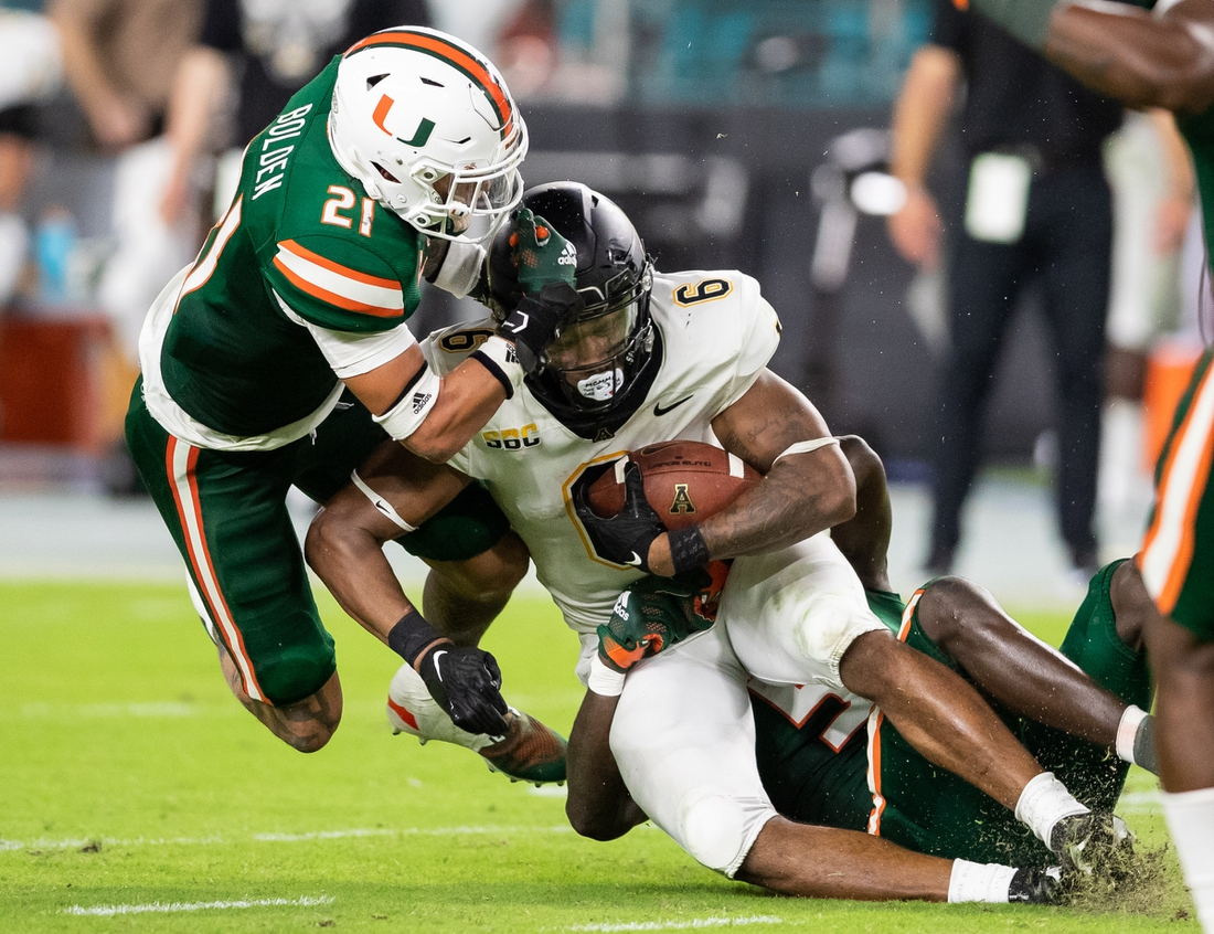 Sep 11, 2021; Miami Gardens, Florida, USA; Appalachian State Mountaineers running back Camerun Peoples (6) is tackled by Miami Hurricanes safety Bubba Bolden (21) and safety Amari Carter (5) during the second quarter at Hard Rock Stadium. Mandatory Credit: Richard Graulich-USA TODAY Sports