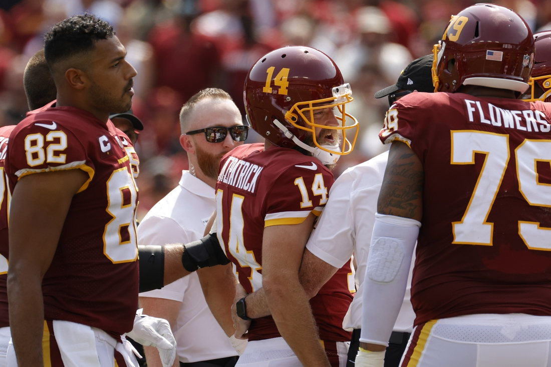 Sep 12, 2021; Landover, Maryland, USA; Washington Football Team quarterback Ryan Fitzpatrick (14) is helped off the field after being inured against the Los Angeles Chargers in the second quarter at FedExField. Mandatory Credit: Geoff Burke-USA TODAY Sports