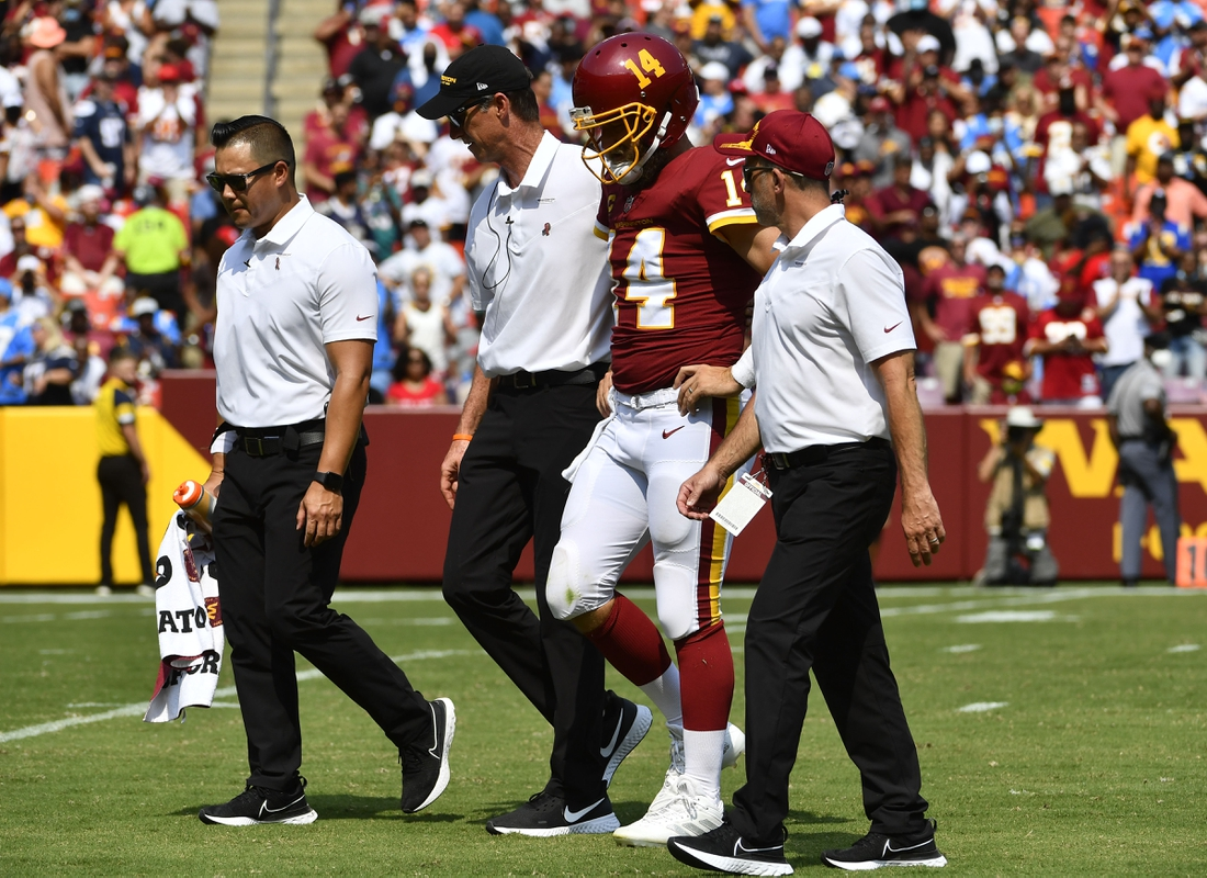 Sep 12, 2021; Landover, Maryland, USA; Washington Football Team quarterback Ryan Fitzpatrick (14) is helped off the field after suffering an injury during the second quarter against the Los Angeles Chargers at FedExField. Mandatory Credit: Brad Mills-USA TODAY Sports