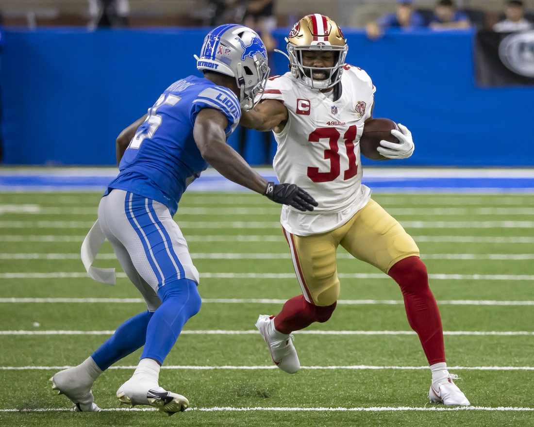 Sep 12, 2021; Detroit, Michigan, USA; San Francisco 49ers running back Raheem Mostert (31) puts a stiff arm to the helmet of Detroit Lions defensive back Will Harris (25) in the first quarter at Ford Field. Mandatory Credit: David Reginek-USA TODAY Sports