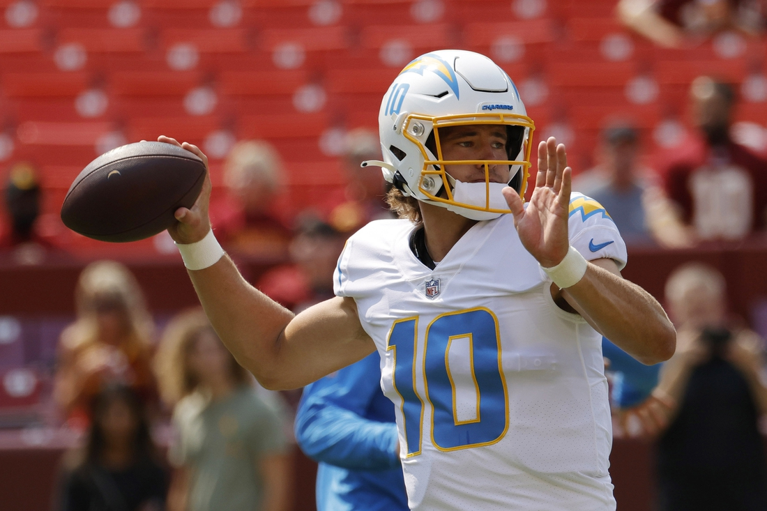 Sep 12, 2021; Landover, Maryland, USA; Los Angeles Chargers quarterback Justin Herbert (10) passes the ball during warmups prior to the Chargers' game against the Washington Football Team at FedExField. Mandatory Credit: Geoff Burke-USA TODAY Sports
