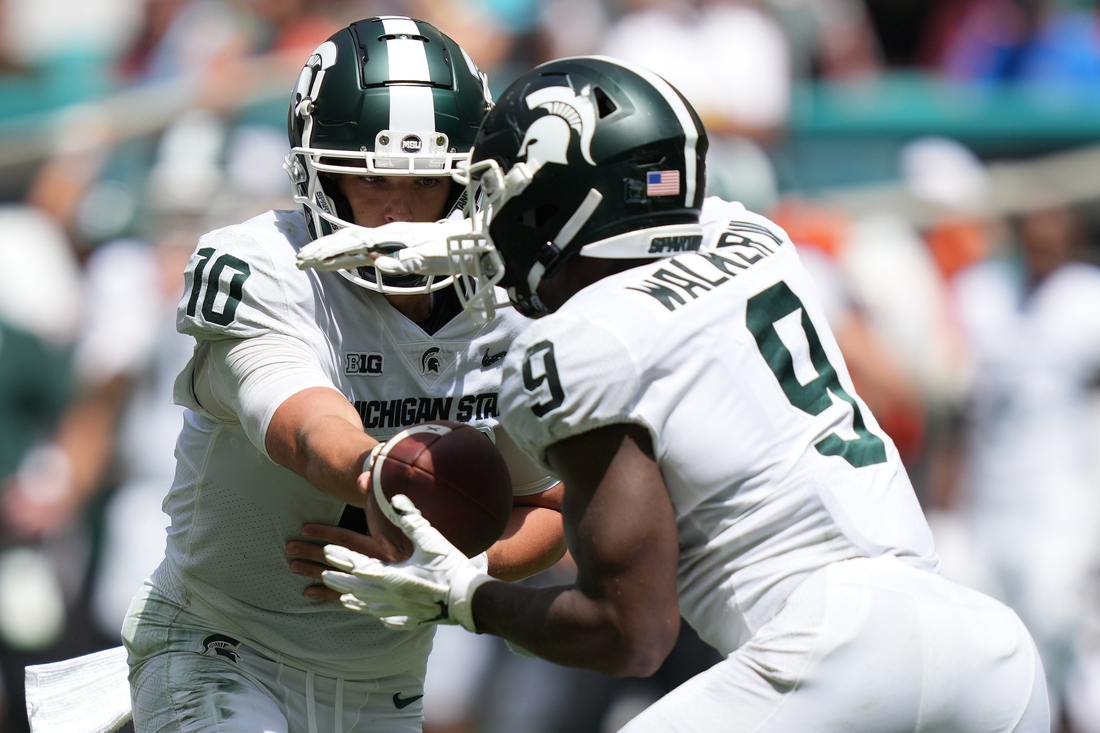 Sep 18, 2021; Miami Gardens, Florida, USA; Michigan State Spartans quarterback Payton Thorne (10) hands the ball to running back Kenneth Walker III (9) during the first half against the Miami Hurricanes at Hard Rock Stadium. Mandatory Credit: Jasen Vinlove-USA TODAY Sports
