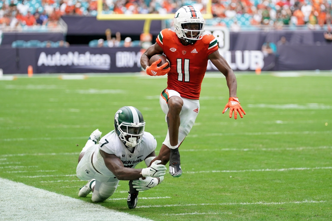 Sep 18, 2021; Miami Gardens, Florida, USA; Miami Hurricanes wide receiver Charleston Rambo (11) breaks the tackle of Michigan State Spartans safety Michael Dowell (7) during the second half at Hard Rock Stadium. Mandatory Credit: Jasen Vinlove-USA TODAY Sports