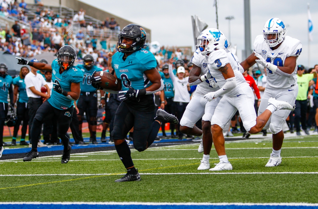 Sep 18, 2021; Buffalo, New York, USA; Coastal Carolina Chanticleers wide receiver Aaron Bedgood (3) turns the ball up field and out runs Buffalo Bulls defensive end Taylor Riggins (49) and cornerback Aapri Washington (3) to score a touchdown giving the Chanticleers an early 7-0 lead during the first quarter of play at UB Stadium. Mandatory Credit: Nicholas LoVerde-USA TODAY Sports