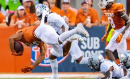 Sep 18, 2021; Austin, Texas; Texas Longhorns running back Bijan Robinson (5) goes airborne after being tripped up by Rice Owl defenders during the first quarter at Darrell K Royal-Texas Memorial Stadium. Mandatory Credit: John Gutierrez-USA TODAY Sports