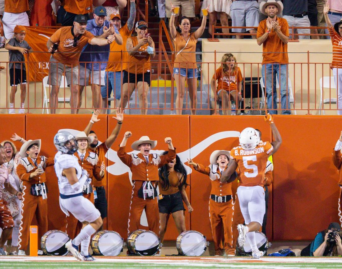Sep 18, 2021; Austin, Texas, USA; Texas Longhorns running back Bijan Robinson (5) celebrates his touchdown with fans against the Rice Owls during the second quarter at Darrell K Royal-Texas Memorial Stadium. Mandatory Credit: John Gutierrez-USA TODAY Sports