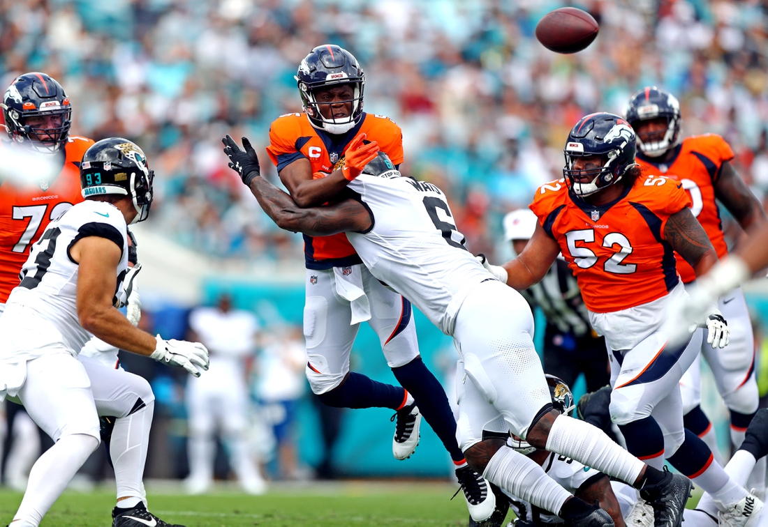 Sep 19, 2021; Jacksonville, Florida, USA; Denver Broncos quarterback Teddy Bridgewater (5) throws a pass while being hit by Jacksonville Jaguars defensive end jihad Ward (6) during the first quarter at TIAA Bank Field. Mandatory Credit: Mark J. Rebilas-USA TODAY Sports