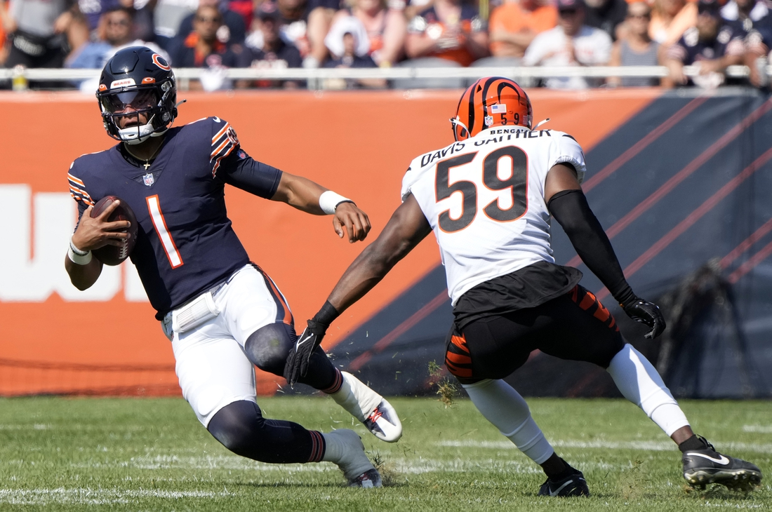 Sep 19, 2021; Chicago, Illinois, USA; Chicago Bears quarterback Justin Fields (1) rushes the ball against Cincinnati Bengals linebacker Akeem Davis-Gaither (59) during the second half at Soldier Field. Mandatory Credit: Mike Dinovo-USA TODAY Sports