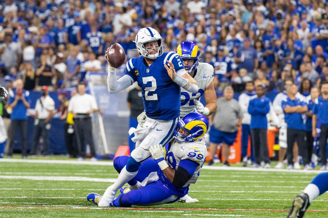 Sep 19, 2021; Indianapolis, Indiana, USA; Indianapolis Colts quarterback Carson Wentz (2) passes the ball while Los Angeles Rams defensive end Aaron Donald (99) defends in the second half at Lucas Oil Stadium. Mandatory Credit: Trevor Ruszkowski-USA TODAY Sports