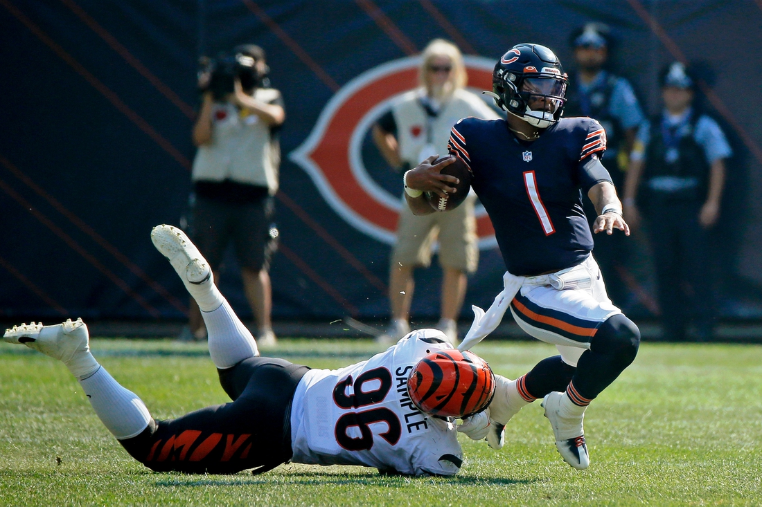 Sep 19, 2021; Chicago, Illinois, USA; Chicago Bears quarterback Justin Fields (1) gets tripped up by Cincinnati Bengals defensive end Cameron Sample (96) during the fourth quarter at Soldier Field. Mandatory Credit: Jon Durr-USA TODAY Sports