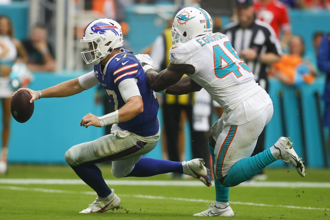 Buffalo Bills quarterback Josh Allen slides near the first-yard line as Miami Dolphins linebacker Sam Eguavoen pushes Allen from behind during the fourth quarter of the game at Hard Rock Stadium.