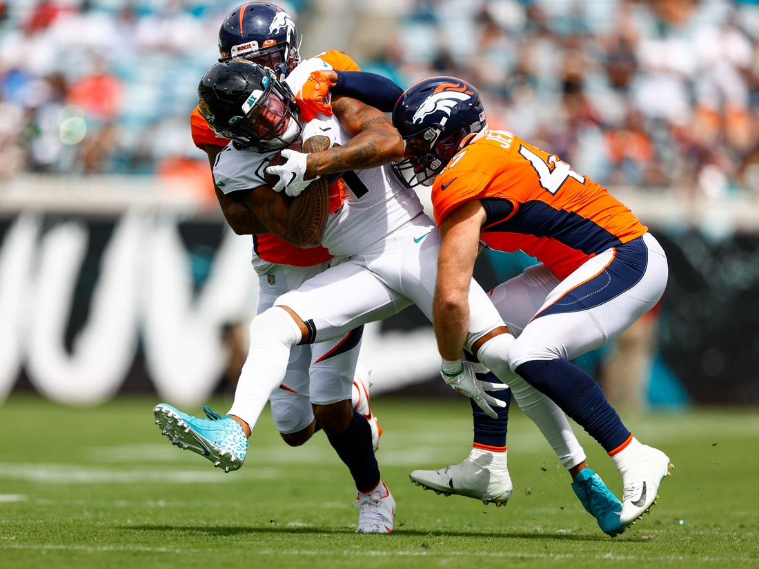 Sep 19, 2021; Jacksonville, Florida, USA;  Jacksonville Jaguars wide receiver Marvin Jones (11) is tackled by Denver Broncos cornerback Pat Surtain II (2) and inside linebacker Josey Jewell (47) in the first quarter  at TIAA Bank Field. Mandatory Credit: Nathan Ray Seebeck-USA TODAY Sports