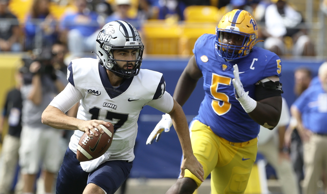 Sep 25, 2021; Pittsburgh, Pennsylvania, USA;  New Hampshire Wildcats quarterback Bret Edwards (17) scrambles with the ball as Pittsburgh Panthers defensive lineman Deslin Alexandre (5) chases during the second quarter at Heinz Field. Mandatory Credit: Charles LeClaire-USA TODAY Sports