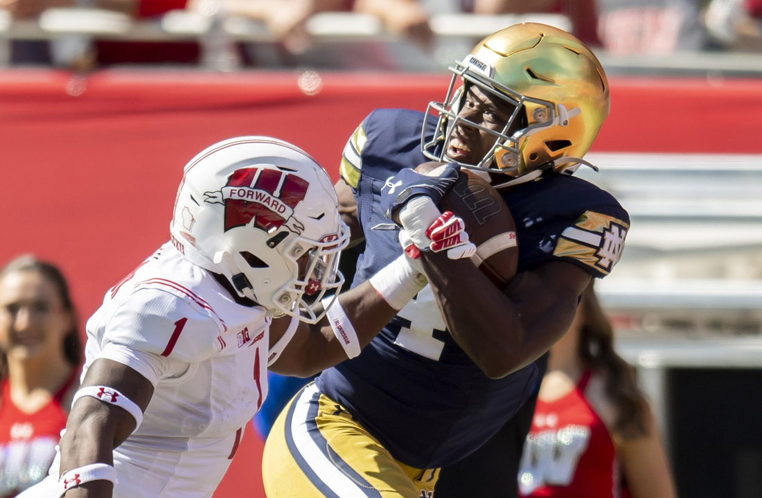 Sep 25, 2021; Chicago, Illinois, USA; Notre Dame Fighting Irish wide receiver Kevin Austin Jr. (4) receives a pass for a touchdown against Wisconsin Badgers cornerback Faion Hicks (1) during the first half at Soldier Field. Mandatory Credit: Patrick Gorski-USA TODAY Sports