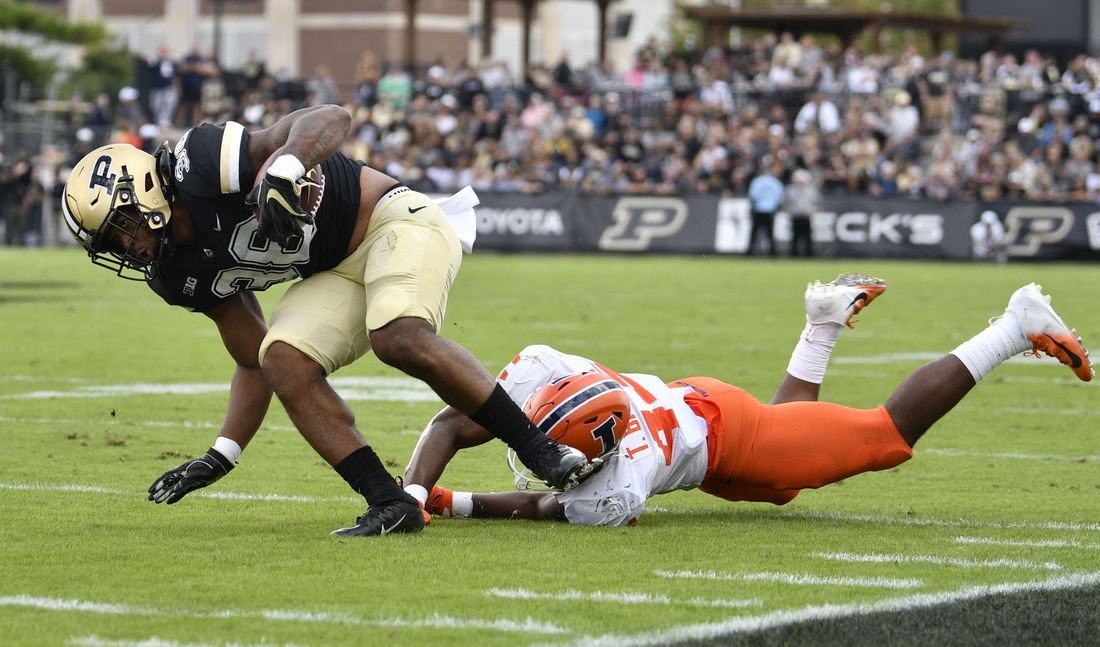 Sep 25, 2021; West Lafayette, Indiana, USA;  Purdue Boilermakers running back Dylan Downing (38) evades a tackle against Illinois Fighting Illini linebacker Tarique Barnes (44) during the first quarter at Ross-Ade Stadium. Mandatory Credit: Marc Lebryk-USA TODAY Sports