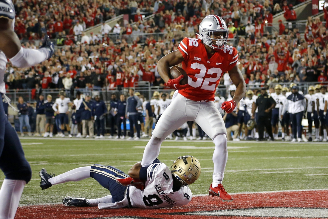 Sep 25, 2021; Columbus, Ohio, USA; Ohio State Buckeyes running back TreVeyon Henderson (32) runs in the touchdown over Akron Zips safety Jaylen Kelly-Powell (8)during the first quarter at Ohio Stadium. Mandatory Credit: Joseph Maiorana-USA TODAY Sports