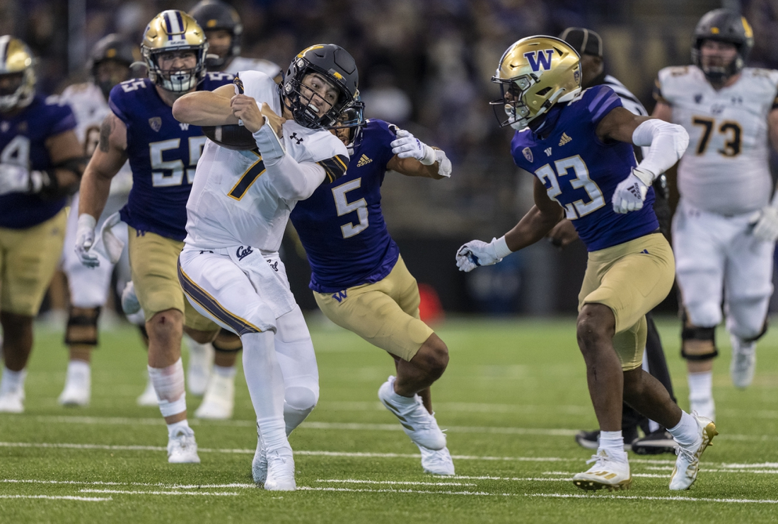 Sep 25, 2021; Seattle, Washington, USA; California Golden Bears quarterback Chase Garbers (7) runs with the ball as Washington Huskies defensive back Alex Cook (5) and defensive back Mishael Powell (23) move in to make a tackle during the second half of a game at Alaska Airlines Field at Husky Stadium. The Huskies won 31-24 in overtime. Mandatory Credit: Stephen Brashear-USA TODAY Sports