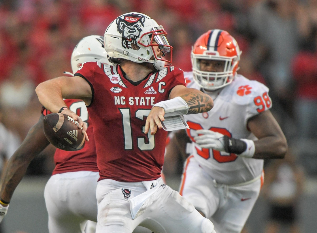 NC State quarterback Devin Leary (13) passes near Clemson defensive end Myles Murphy (98) during the fourth quarter at Carter-Finley Stadium in Raleigh, N.C., September 25, 2021.  The Tigers lost 27-21 in two overtimes game at Carter-Finley Stadium in Raleigh, N.C., September 25, 2021. Leary  was 32-44 for 238  yards and four touchdown passes.  Ncaa Football Clemson At Nc State