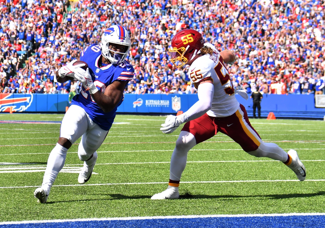 Sep 26, 2021; Orchard Park, New York, USA; Buffalo Bills running back Zack Moss (20) scores a touchdown beating Washington Football Team linebacker Cole Holcomb (55) to the end zone in the second quarter at Highmark Stadium. Mandatory Credit: Mark Konezny-USA TODAY Sports