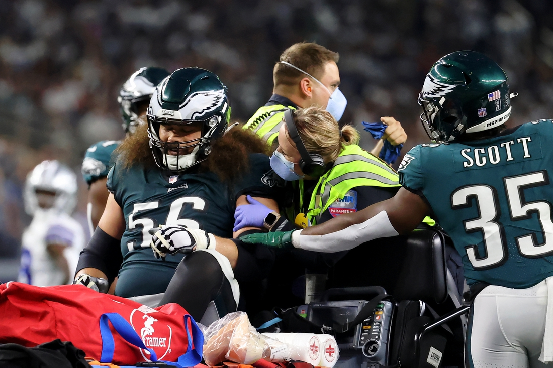 Sep 27, 2021; Arlington, Texas, USA; Philadelphia Eagles offensive guard Isaac Seumalo (56) is consoled by running back Boston Scott (35) as he is taken off the field on a cart after sustaining an apparent injury during the fourth quarter of their game against the Dallas Cowboys at AT&T Stadium. Mandatory Credit: Kevin Jairaj-USA TODAY Sports