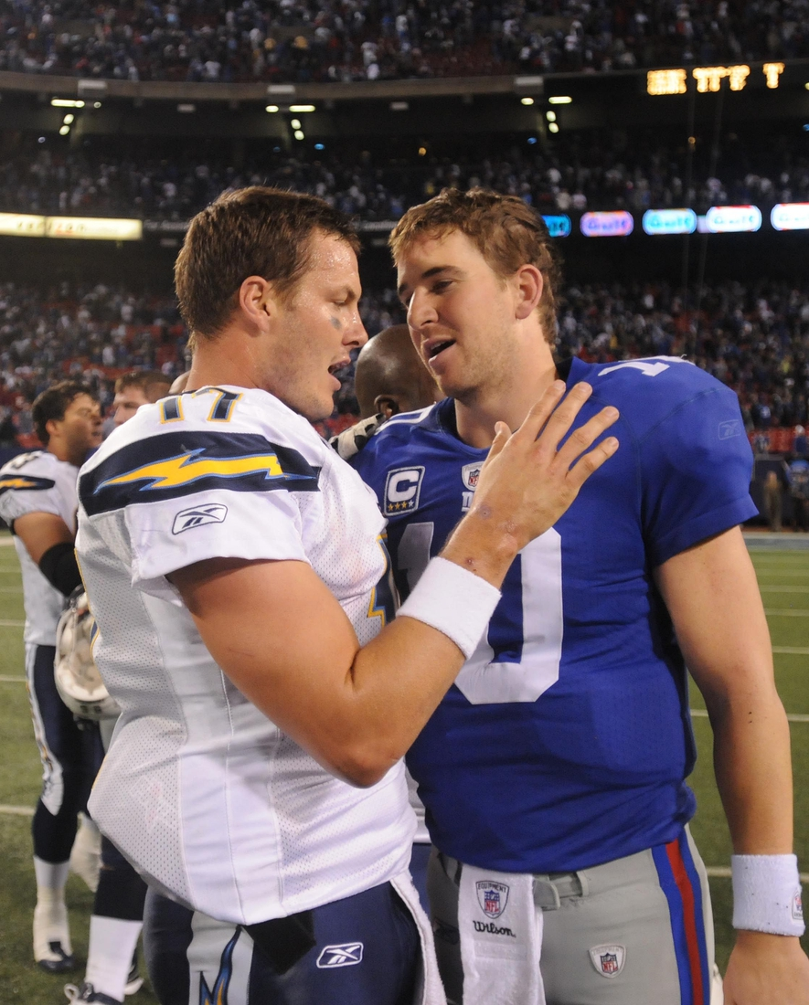 In this November 8, 2009 photo, Giants QB Eli Manning and San Diego Charges QB Philip Rivers come together at the end of the Giants 21-20 loss Sunday at Giants Stadium.  8fh00lbz