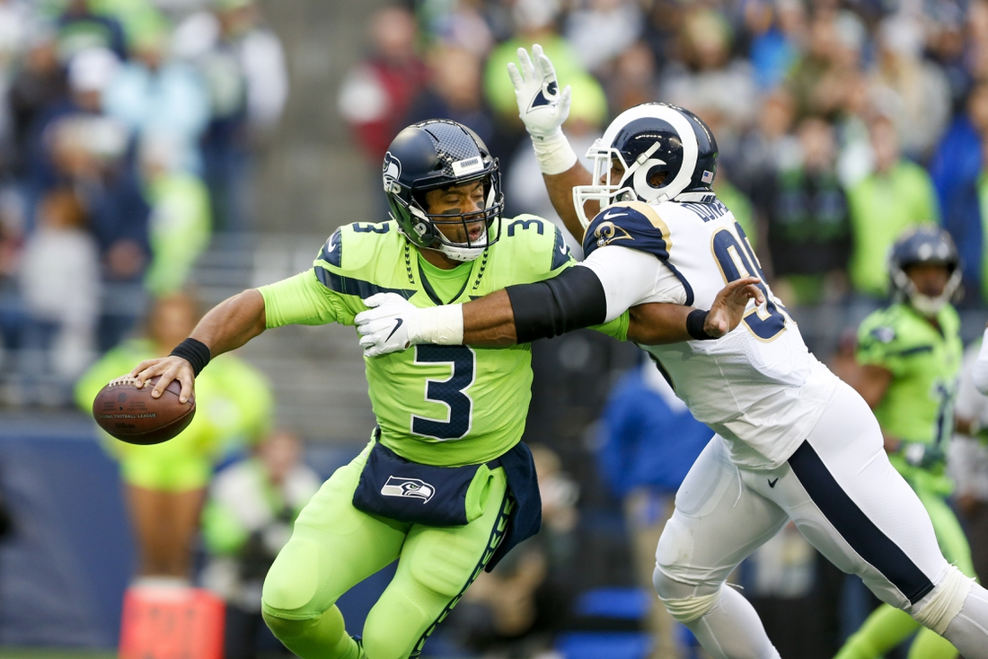 Oct 3, 2019; Seattle, WA, USA; Los Angeles Rams defensive tackle Aaron Donald (99) pressures Seattle Seahawks quarterback Russell Wilson (3) during the first quarter at CenturyLink Field. Mandatory Credit: Joe Nicholson-USA TODAY Sports