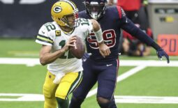 Oct 25, 2020; Houston, Texas, USA; Green Bay Packers quarterback Aaron Rodgers (12) scrambles with the ball as Houston Texans outside linebacker Whitney Mercilus (59) defends during the first quarter at NRG Stadium. Mandatory Credit: Troy Taormina-USA TODAY Sports
