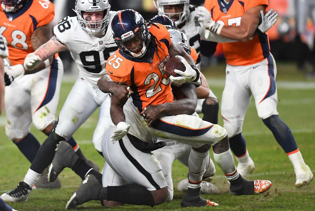 Jan 3, 2021; Denver, Colorado, USA; Denver Broncos running back Melvin Gordon (25) is tackled in the fourth quarter against the Las Vegas Raiders at Empower Field at Mile High. Mandatory Credit: Ron Chenoy-USA TODAY Sports