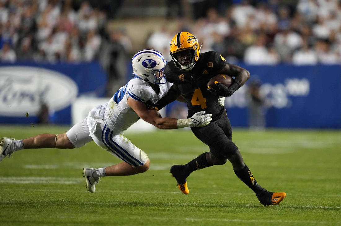 Sep 18, 2021; Provo, Utah, USA; Arizona State Sun Devils running back Daniyel Ngata (4) is defended by BYU Cougars linebacker Payton Wilgar (49) in the second half at LaVell Edwards Stadium. Mandatory Credit: Kirby Lee-USA TODAY Sports