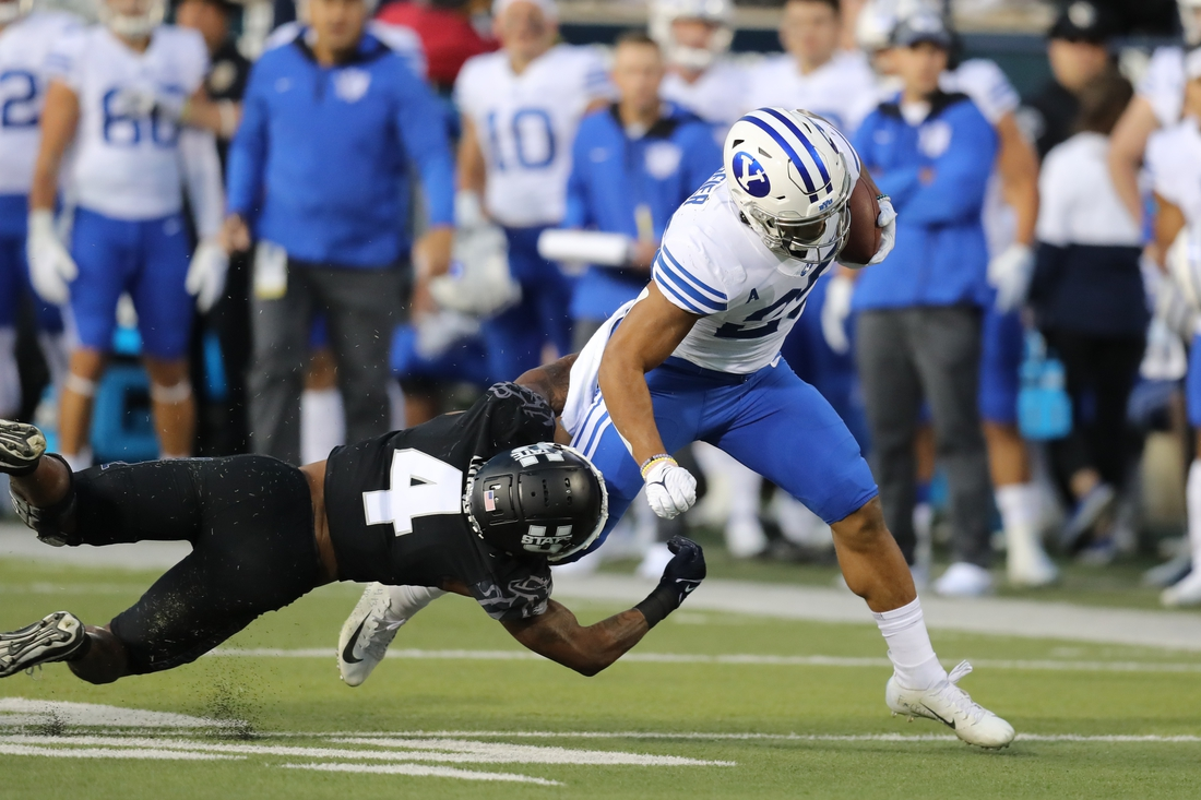Oct 1, 2021; Logan, Utah, USA; Utah State Aggies running back Calvin Tyler Jr. (4) attempts to tackle Brigham Young Cougars defensive back Talan Alfrey (25) as he runs for a touchdown during the first quarter at Merlin Olsen Field at Maverik Stadium. Mandatory Credit: Rob Gray-USA TODAY Sports