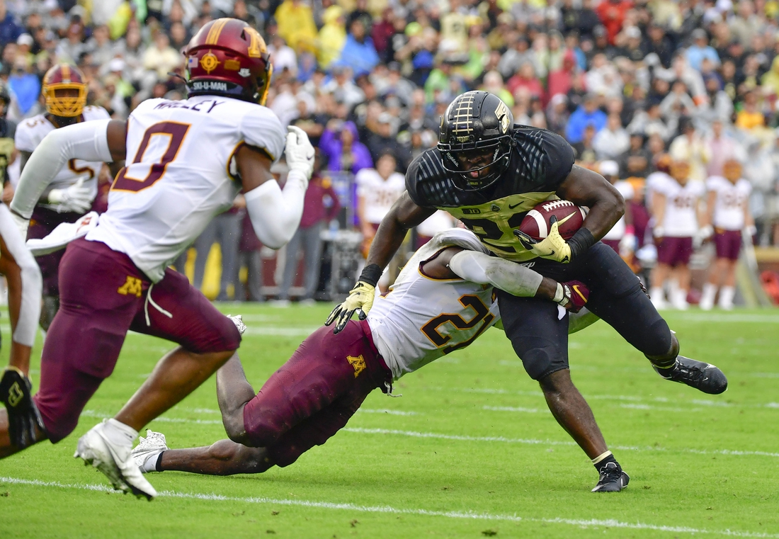 Oct 2, 2021; West Lafayette, Indiana, USA;  Purdue Boilermakers running back King Doerue (22) is tackled by Minnesota Golden Gophers defensive back Justus Harris (21) during the second quarter at Ross-Ade Stadium. Mandatory Credit: Marc Lebryk-USA TODAY Sports