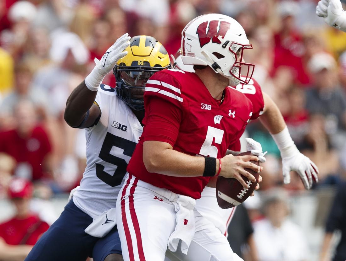 Oct 2, 2021; Madison, Wisconsin, USA;  Wisconsin Badgers quarterback Graham Mertz (5) is sacked by Michigan Wolverines linebacker David Ojabo (55) during the second quarter at Camp Randall Stadium. Mandatory Credit: Jeff Hanisch-USA TODAY Sports