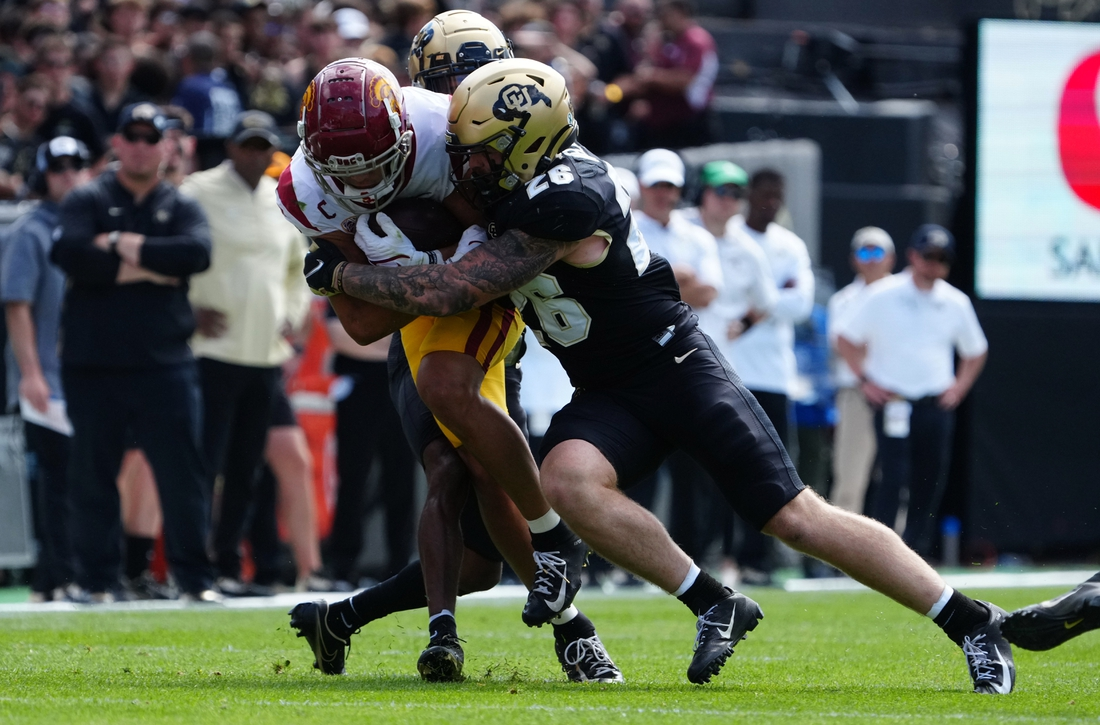 Oct 2, 2021; Boulder, Colorado, USA; Colorado Buffaloes linebacker Carson Wells (26) tackles USC Trojans wide receiver Drake London (15) in the second quarter at Folsom Field. Mandatory Credit: Ron Chenoy-USA TODAY Sports