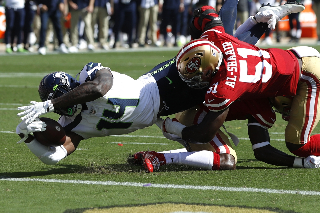 Oct 3, 2021; Santa Clara, California, USA; Seattle Seahawks wide receiver DK Metcalf (14) dives for the end zone while being tackled by San Francisco 49ers linebacker Azeez Al-Shaair (51) and cornerback Jimmie Ward (1) during the second quarter at Levi's Stadium. Mandatory Credit: Darren Yamashita-USA TODAY Sports
