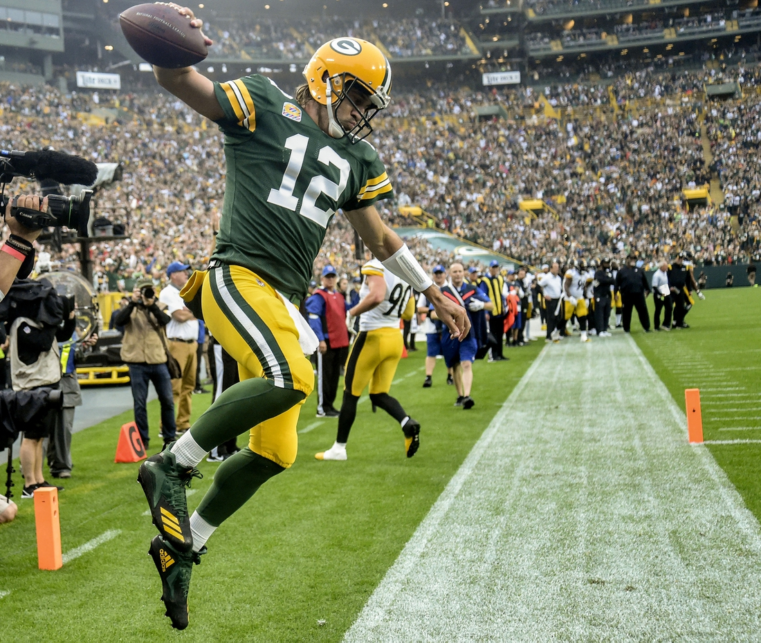 Oct 3, 2021; Green Bay, Wisconsin, USA; Green Bay Packers quarterback Aaron Rodgers (12) celebrates after scoring a touchdown in the second quarter against the Pittsburgh Steelers at Lambeau Field. Mandatory Credit: Benny Sieu-USA TODAY Sports