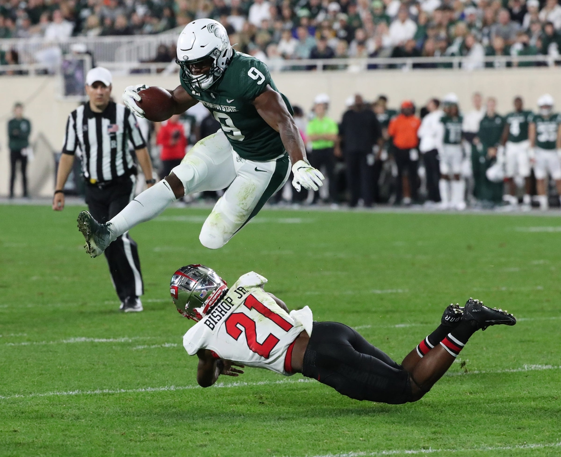 Michigan State Spartans running back Kenneth Walker III jumps over Western Kentucky Hilltoppers defensive back Beanie Bishop on Saturday, Oct. 02, 2021.  Msu Wku