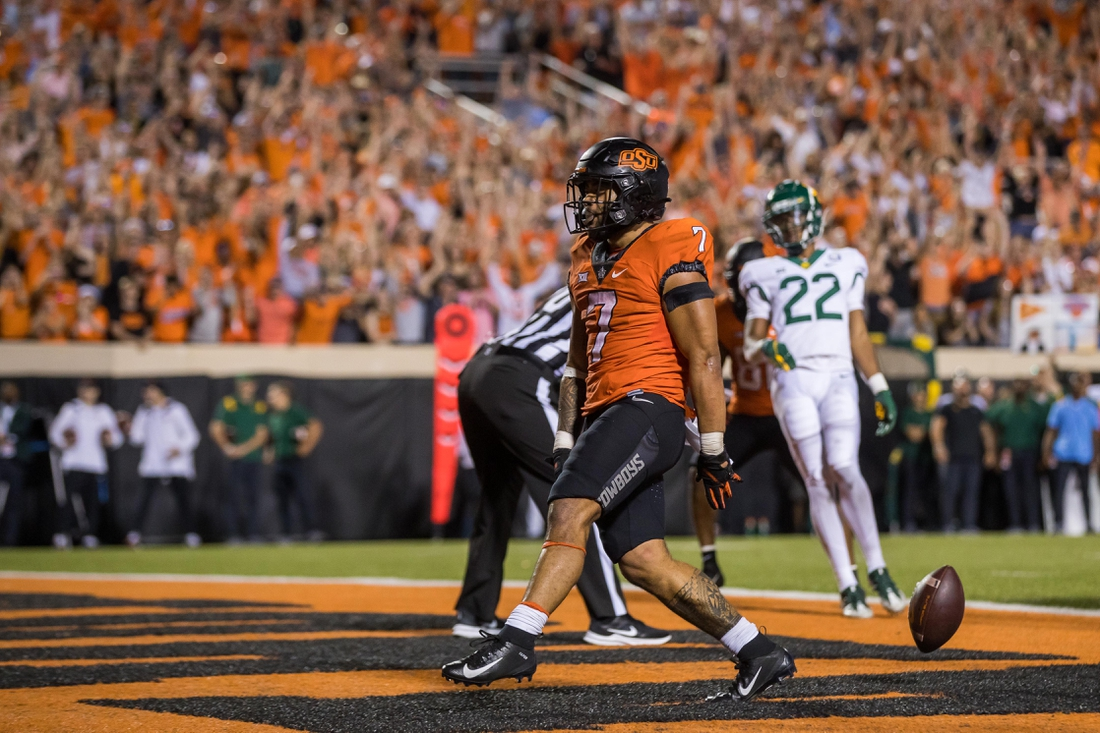 Oct 2, 2021; Stillwater, Oklahoma, USA;  Oct 2, 2021; Stillwater, Oklahoma, USA; Oklahoma State Cowboys running back Jaylen Warren (7) drops the ball after scoring a touchdown during the fourth quarter against the Baylor Bears at Boone Pickens Stadium. OSU won 24-14. Mandatory Credit: Brett Rojo-USA TODAY Sports