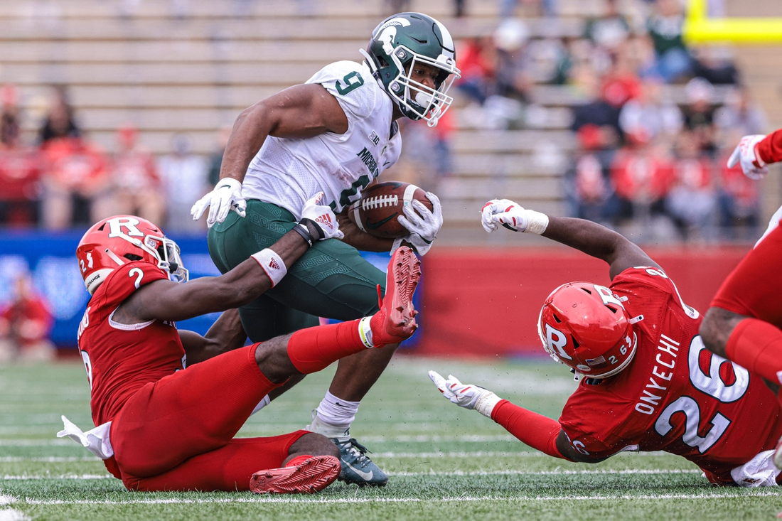 Oct 9, 2021; Piscataway, New Jersey, USA; Michigan State Spartans running back Kenneth Walker III (9) is tackled by Rutgers Scarlet Knights defensive back Avery Young (2) and defensive lineman CJ Onyechi (26) during the second half at SHI Stadium. Mandatory Credit: Vincent Carchietta-USA TODAY Sports