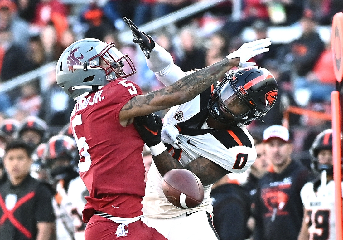 Oct 9, 2021; Pullman, Washington, USA; Washington State Cougars defensive back Derrick Langford (5) is called for pass interference on his play against Oregon State Beavers wide receiver Tre'Shaun Harrison (0) in the first half at Gesa Field at Martin Stadium. Mandatory Credit: James Snook-USA TODAY Sports