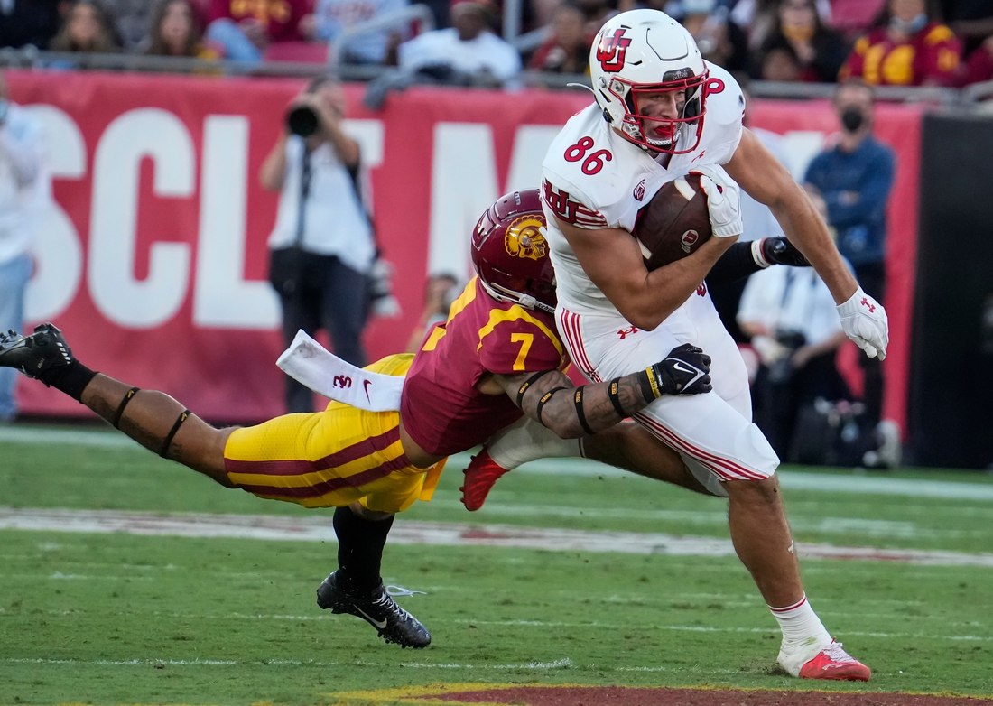 Oct 9, 2021; Los Angeles, California, USA; USC Trojans safety Chase Williams (7) makes a diving tackle on Utah Utes tight end Dalton Kincaid (86) during the second quarter at United Airlines Field at Los Angeles Memorial Coliseum. Mandatory Credit: Robert Hanashiro-USA TODAY Sports