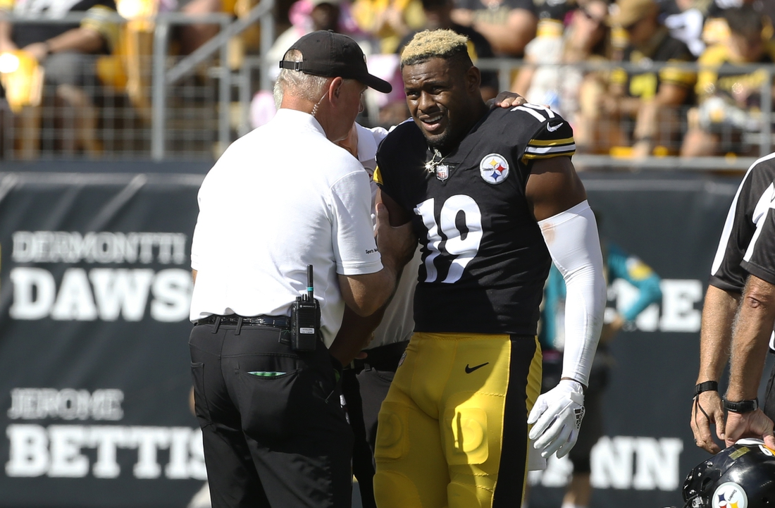 Oct 10, 2021; Pittsburgh, Pennsylvania, USA;  Pittsburgh Steelers team orthopedic doctor James Bradley (left) looks at the right arm of Pittsburgh Steelers wide receiver JuJu Smith-Schuster (19) after Smith-Schuster suffered an apparent injury against the Denver Broncos during the second quarter at Heinz Field. Smith-Schuster  would leave the game. Mandatory Credit: Charles LeClaire-USA TODAY Sports