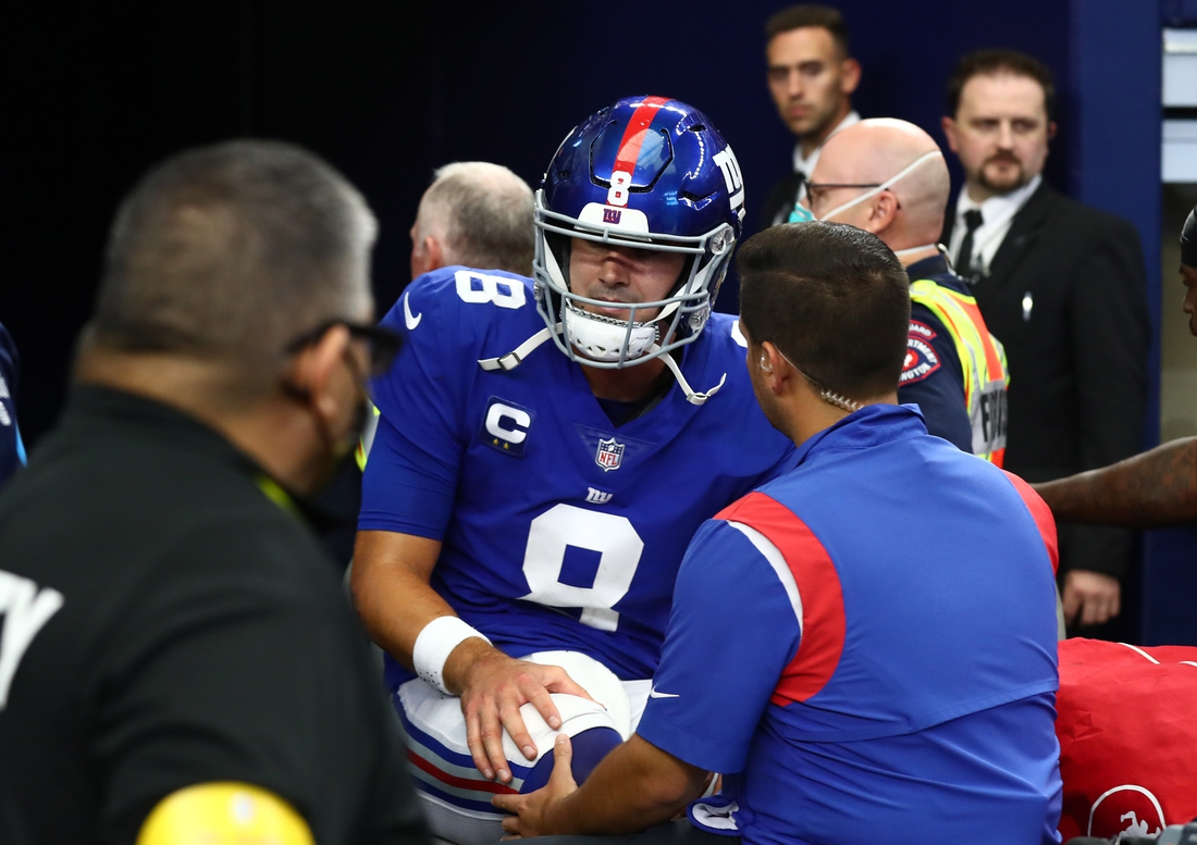 Oct 10, 2021; Arlington, Texas, USA; New York Giants quarterback Daniel Jones (8) holds his right knee as he heads to the locker room on a medical cart in the first half during the game against the Dallas Cowboys at AT&T Stadium. Mandatory Credit: Matthew Emmons-USA TODAY Sports