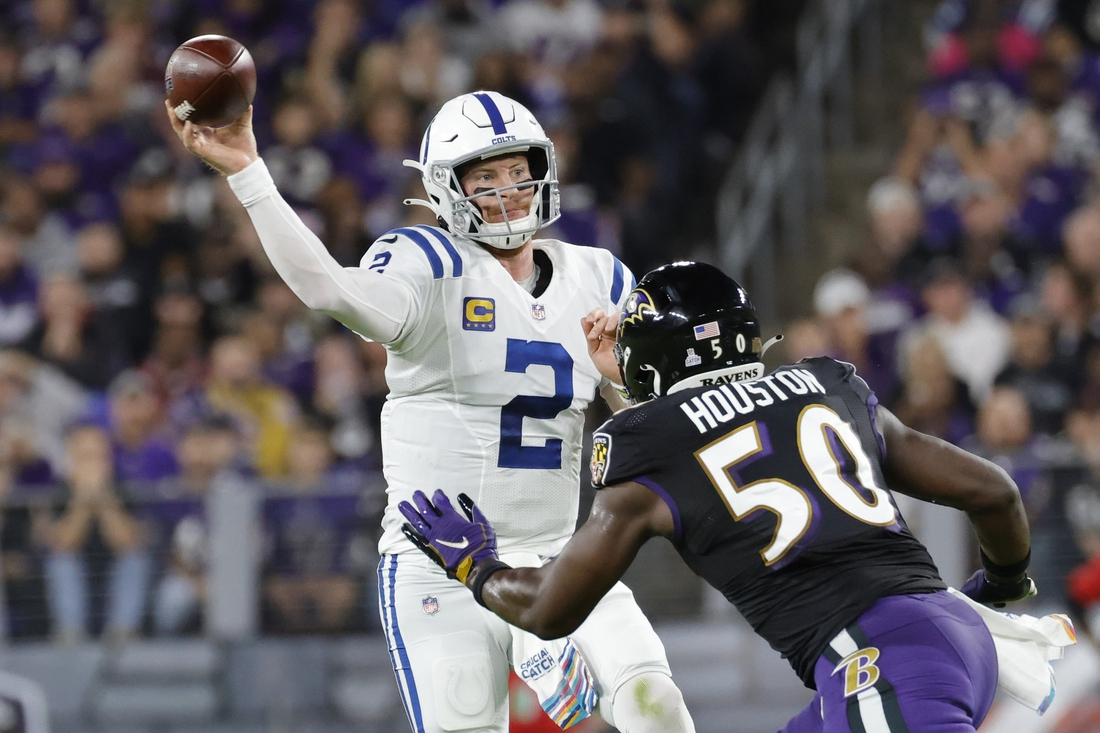 Oct 11, 2021; Baltimore, Maryland, USA; Indianapolis Colts quarterback Carson Wentz (2) passes the ball under pressure from Baltimore Ravens outside linebacker Justin Houston (50) during the first quarter at M&T Bank Stadium. Mandatory Credit: Geoff Burke-USA TODAY Sports
