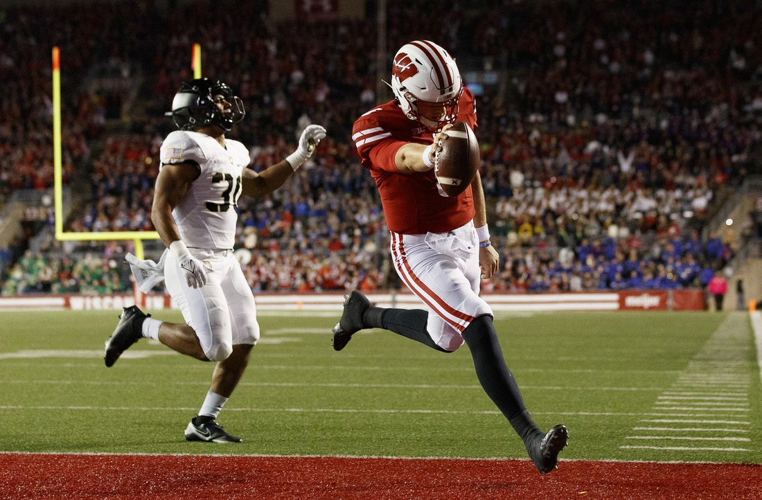 Oct 16, 2021; Madison, Wisconsin, USA;  Wisconsin Badgers quarterback Graham Mertz (5) rushes for a touchdown in front of Army Black Knights linebacker Daryan McDonald (30) during the second quarter at Camp Randall Stadium. Mandatory Credit: Jeff Hanisch-USA TODAY Sports