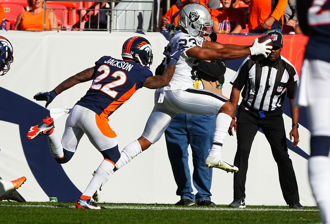 Oct 17, 2021; Denver, Colorado, USA; Las Vegas Raiders running back Kenyan Drake (23) leaps past Denver Broncos safety Kareem Jackson (22) to score a touchdown in the second quarter at Empower Field at Mile High. Mandatory Credit: Ron Chenoy-USA TODAY Sports